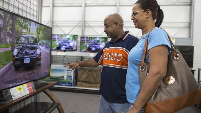 FILE - In this Aug. 17, 2014, file photo, Robert and Doreen Walcott, of Easton, check out televisions at Best Buy in Brockton during tax-free weekend.