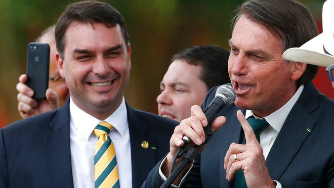This Nov. 21, 2019 file photo shows Sen. Flavio Bolsonaro, left, with his father Brazilian President Jair Bolsonaro at the launch of his father's new political party Alliance for Brazil in Brasilia, Brazil. Public prosecutors in Rio de Janeiro state have indicted Sen. Flávio Bolsonaro for allegedly commanding a criminal organization and laundering money when he was a state lawmaker between 2007 and 2018, according to a statement the public prosecutors' office posted to its website on Wednesday, Nov. 4, 2020.