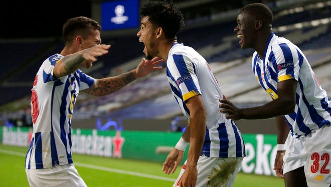 Porto's Luis Diaz celebrates with Otavio, left, and Malang Sarr, right, after scoring his side's third goal during the Champions League group C soccer match between FC Porto and Olympique de Marseille at the Dragao stadium in Porto, Portugal, Tuesday, Nov. 3, 2020.