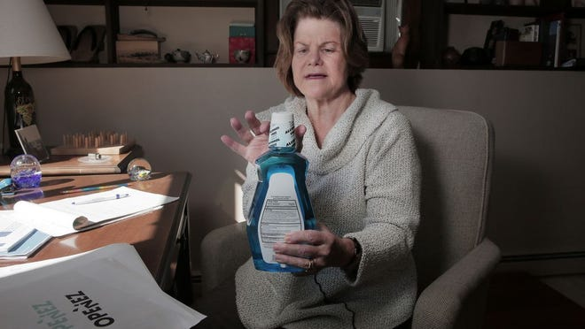 Retired nurse Hannah Boulton studies the hard-to-open packaging of some products such as mouthwash at her home office in Duxbury on Friday October 9, 2020. Boulton founded a business to make packages easier for seniors to open after seeing many examples of bad, even unsafe packaging in her work. Photo by Lauren Owens Lambert / for The Patriot Ledger.