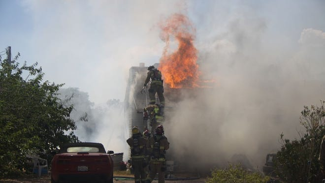 KCFD descends after creating a hole on the roof, allowing firefighters more access to the flames.