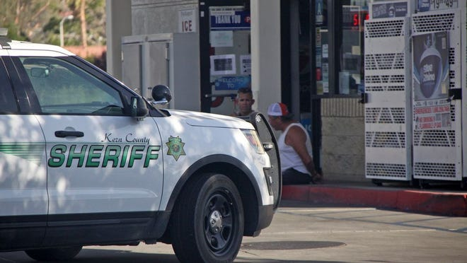 George Smith, in white tank top, sits on a curb at the Arco gas station during his arrest June 30 on charges of murder, arson and felony evading of a police officer.