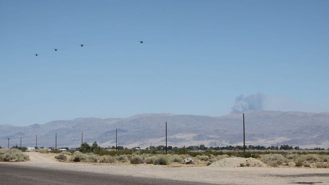 Four helicopters head toward a plume of smoke from a fire located within the boundaries of Naval Air Weapons Station China Lake on Thursday. The fire began Wednesday afternoon.