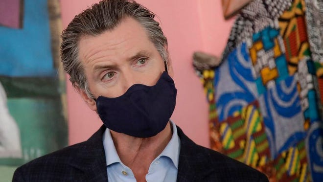 Gov. Gavin Newsom wears a protective mask on his face while speaking to reporters at Miss Ollie's restaurant during the coronavirus outbreak in Oakland on Tuesday, June 9, 2020.
