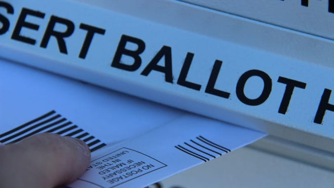 A Kern County voter deposits a vote-by-mail ballot at the library in Ridgecrest Oct. 30, 2020.