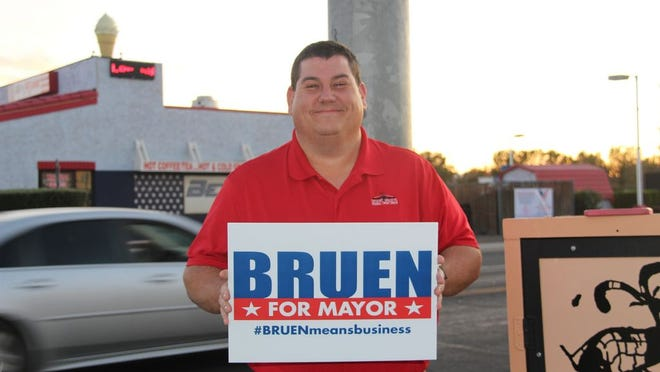 Eric Bruen holds a campaign sign Tuesday evening. Bruen has won the race for Ridgecrest mayor according to unofficial final results from Kern County.
