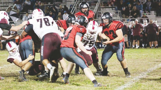 Ravenswood players team up to tackle a Roane County Raider during a regular season game last fall.