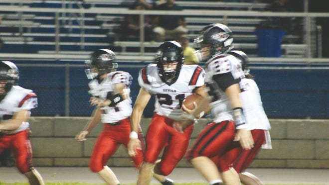Senior Case Fletcher, No. 21, controls the ball for the Red Devils in an attempt to earn the first-down.