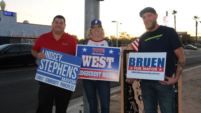 Pictured: three of four council candidates for mayor, from left Bruen, Lindsey Stephens and Christian West swapped signs for a light-hearted moment as their campaigns wound down Tuesday evening.