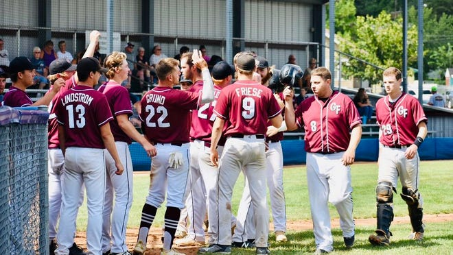 Teammates emerge from the dugout to welcome in Listul on home run.
