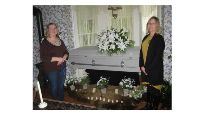 Leslie Gilliland Harkai (left) and Patty Sherman, president of the Flat Rock Historical Society, stand in front of a flocked cloth casket in a parlor room at the Langs-Wager House. This was a photo taken in 2017 in advance of the first Historic Cemetery Walk hosted by the Brownstown Township and Flat Rock historical societies. The Flat Rock Historical Society has now won an award for this event.