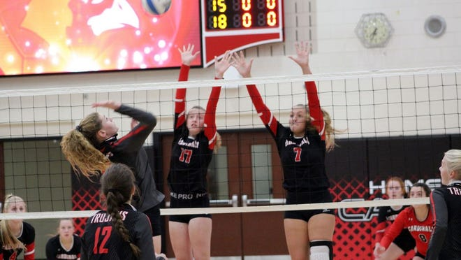 Eighth-grader Kendall Huhnerkoch (17) teams up with veteran Sydney Sommers (7) at the net in the Cardinals recent 3-0 win over Worthington.