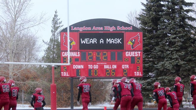 The Langdon Area High School scoreboard advises fans to wear a mask during a game against Thompson on Oct. 24 at Langdon Area High School. Masks are required to enter football games at Langdon Area High School.