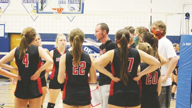 Ravenswood's volleyball coach Chris Michael discusses strategy with his Red Devilettes during a regular season game.