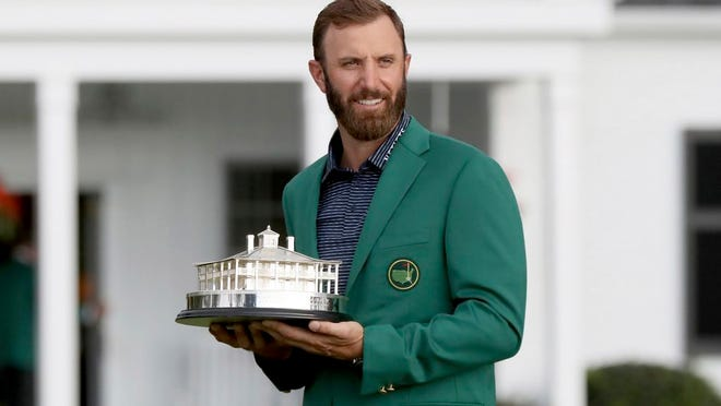Dustin Johnson holds the trophy after being presented with his first green jacket after winning the Masters golf tournament Sunday, Nov. 15, 2020, in Augusta, Ga.