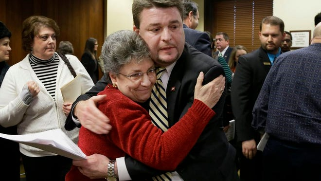 Sen. Jason Rapert, R-Conway, center, gets a hug from Dorothy Troglin, a supporter of Rapert's bill that would ban abortions if a heartbeat is detected 12 weeks into a pregnancy, after the bill passed a vote in the House Committee on Public Health, Welfare and Labor at the Arkansas state Capitol in Little Rock, Ark., Thursday, Feb. 7, 2013. Arkansas Gov. Mike Beebe said Thursday he'll sign into law legislation prohibiting insurers from covering most abortions in an exchange created under the federal health care law, as lawmakers advanced a separate measure banning the procedure 12 weeks into a pregnancy.