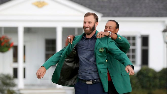 Last year's Masters champion Tiger Woods, right, presents Dustin Johnson his first green jacket after winning the Masters golf tournament Sunday, Nov. 15, 2020, in Augusta, Ga.