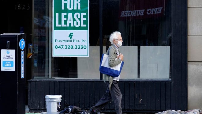"In this Nov. 6, 2020, file photo, a man walks past an empty store with a ""For Lease"" sign in downtown Evanston, Ill."