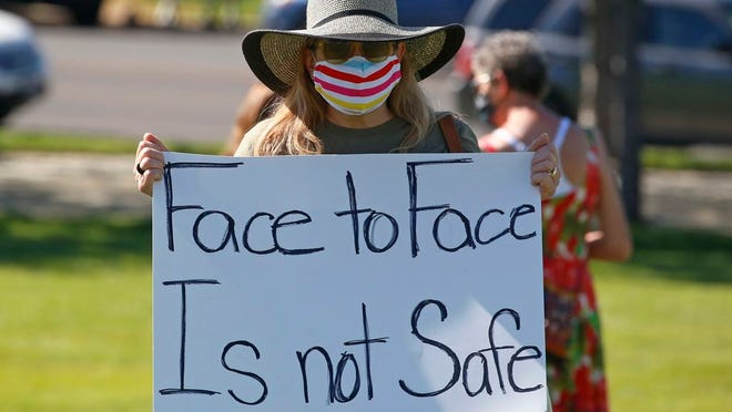 Kris Reddout, a 5th grade teacher, attends a Utah Safe Schools Mask-In urging the governor's leadership in school reopening during a rally Thursday, July 23, 2020, in Salt Lake City. Parents and teachers rallied at the Utah State Capitol Thursday morning to urge schools to enforce mask wearing and to implement other safety policies recommended by health officials as the state prepares to reopen classrooms this fall.