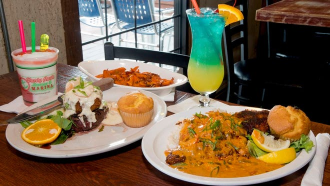 Two popular dishes at Shorty Pants: the surf and turf features a center cut filet mignon topped with a crab cake, and the smothered catfish.