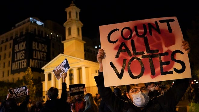 A demonstrator holds up a sign while waiting for election results at Black Lives Matter Plaza, Tuesday, Nov. 3, 2020, in Washington.