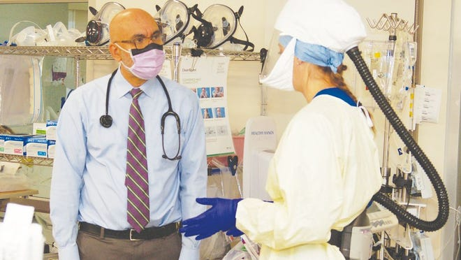 Dr. Harbaksh Sangha, M.D., talks with Dana Becker, R.N., in the ICU, where Becker is preparing to care for a COVID-19 patient.