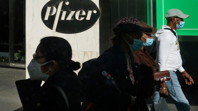 Pedestrians walk past Pfizer world headquarters in New York on Monday Nov. 9, 2020. Pfizer says an early peek at its vaccine data suggests the shots may be 90% effective at preventing COVID-19, but it doesn't mean a vaccine is imminent.