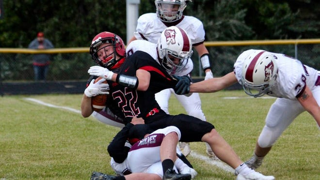 Sophomore running back Colton Schneider powers through four Watford City defenders in a game against the Wolves on Sept. 11 at Joe Roller Field. The Firebirds won, 18-0.