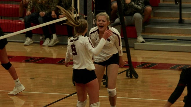 Senior middle hitter Lexis Olson celebrates freshman setter Jalynn Swanson after a Cardinal point in a game against Thompson on Oct. 10 at Langdon Area High School. The Cardinals won 3-1.