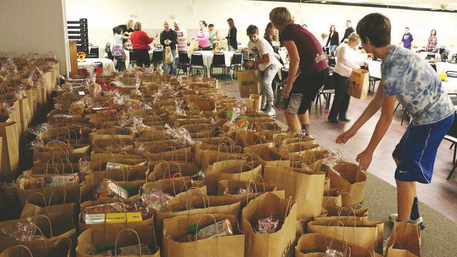 An assembly line forms as volunteers organize full bags of nonperishable food items in 2015 during an Ellis County Ministerial Alliance Thanksgiving Day Feast. This year, the free feast will be a drive-thru food pickup event.