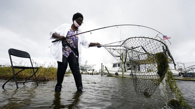 Minnie Lewis fishes for crabs before the wind and waves kick up, in Chalmette, La., Wednesday, Oct. 28, 2020.  Hurricane Zeta is expected to make landfall this afternoon as a category 2 storm.