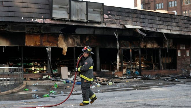 A member of the St. Louis Fire Department removes a hose outside a vandalized and burned convenience store Tuesday, June 2, 2020, in St. Louis. On Monday night people were seen removing items from the store before the building went up in flames and after a large peaceful protest against the death of George Floyd who died after being restrained by Minneapolis police officers on May 25 had ended.