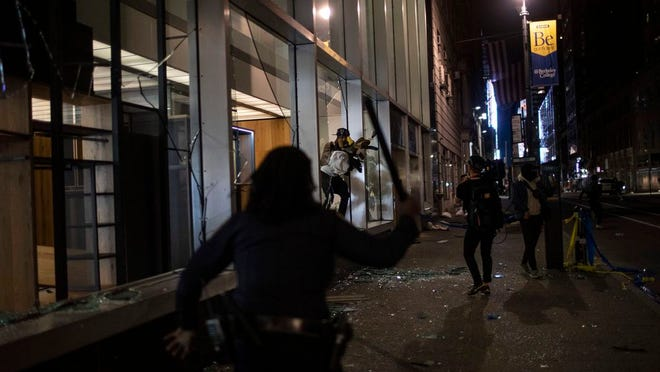 APTOPIX America Protests New York Image ID : 20154141744115 Police run towards people as they jump out of a store with items they took hours after a solidarity rally calling for justice over the death of George Floyd Monday, June 1, 2020, in New York. Floyd died after being restrained by Minneapolis police officers on May 25.