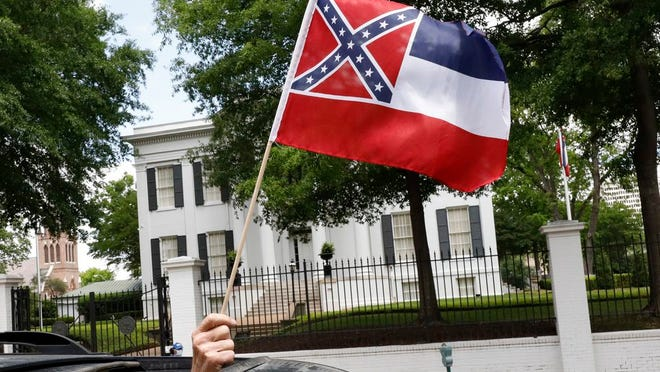 """In this April 25, 2020 photograph, a small Mississippi state flag is held by a participant during a drive-by """"re-open Mississippi"""" protest past the Governor's Mansion, in the background, in Jackson, Miss. This current flag has in the canton portion of the banner the design of the Civil War-era Confederate battle flag, that has been the center of a long-simmering debate about its removal or replacement."""