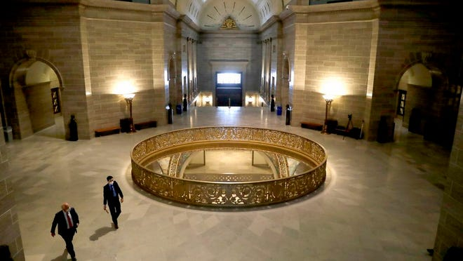 People wear protective masks as they walk in the rotunda at the state Capitol Monday, April 27, 2020, in Jefferson City, Mo. Members of the House returned Monday to begin debate on the budget for the upcoming fiscal year, a daunting task amid declining revenue because of the coronavirus.