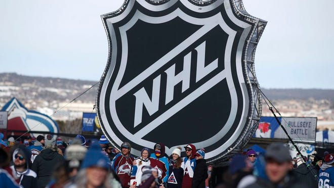 In this Feb. 15, 2020, file photo, fans pose below the NHL league logo at a display outside Falcon Stadium before an NHL Stadium Series outdoor hockey game between the Los Angeles Kings and Colorado Avalanche, at Air Force Academy, Colo.