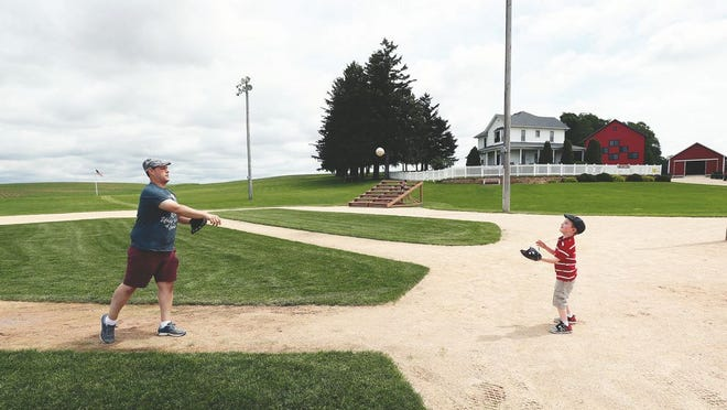 Jeremiah Bronson, of Ames, Iowa, plays catch with his sone Ben, right, on the field at the Field of Dreams movie site, Friday, June 5, 2020, in Dyersville, Iowa.