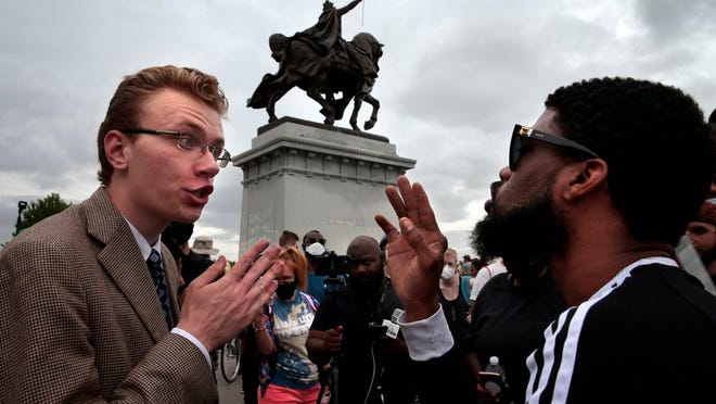 """Mark Williams, left, of Sullivan, Mo., debates the worthiness of a statue of King Louis IX in Forest Park with a man who gave his name as Horus during a rally that brought various opinions to the top of Art Hill on Saturday, June 27, 2020, St. Louis. """"This is hate against the Catholic church,"""" said Williams, calling for a conversion of St. Louis residents. """"If 99 percent of people are Catholic, our racial problems go away."""""""