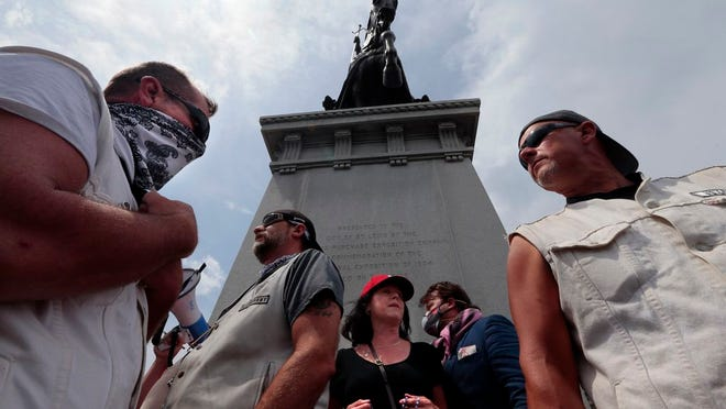 """Members of the Invaders Motorcycle Club step between factions in the fight to decide the future of the King Louis IX statue in Forest Park as statue supporter Beverly Miloscia of Barnhart prays the rosary on Saturday, June 27, 2020, in St, Louis. """"They're not going to be satisfied with statues,"""" said Miloscia. """"People are next."""""""