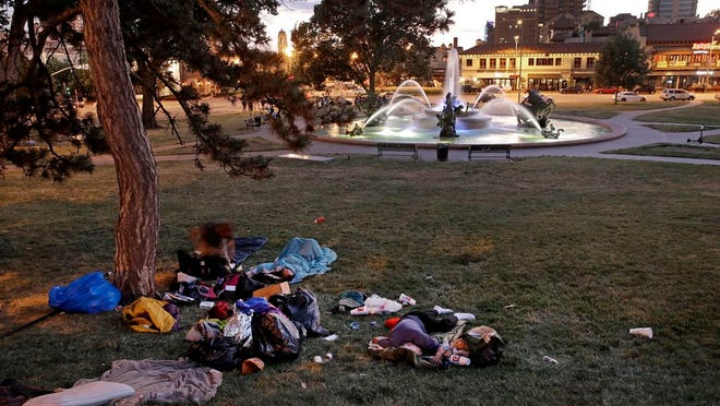 In this photo taken Tuesday, June 23, 2020, homeless people rest on the grass near the J.C. Nichols fountain in Kansas City, Mo. The city's board of parks and recreation is considering a proposal to remove the J.C. Nichols name from the fountain and a nearby street as they address racial concerns about the influential local developer. Nichols developed some of the area's most desirable neighborhoods as well as the city's County Club Plaza shopping district in the early 1900's but excluded Blacks, Jews and other minorities using deed restrictions on his properties.