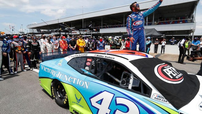In this June 22, 2020, file photo, Bubba Wallace takes a selfie of himself and of other drivers who had pushed his car to the front in the pits at Talladega Superspeedway before the NASCAR Cup Series auto race in Talladega Ala., Monday June 22, 2020.
