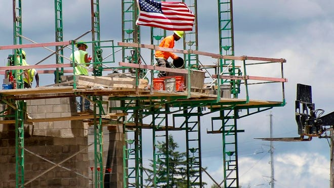 """FILE - In this June 11, 2020, file photo workers on scaffolding lay blocks on one of the larger buildings at a development site where various residential units and commercial sites are under construction in Cranberry Township, Butler County, Pa. Eighty-five percent of Democrats call economic conditions """"poor,"""" while 65% of Republicans describe them as """"good,"""" according to a new survey by The Associated Press-NORC Center for Public Affairs Research."""