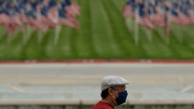 A man wears a face mask as he walks in a park in Kansas City, Mo., during the coronavirus pandemic. The state health department Tuesday raised the death toll by 17, to 1,015, and added more than 500 confirmed cases to the statewide tally, raising it to 21,551 since the pandemic started.