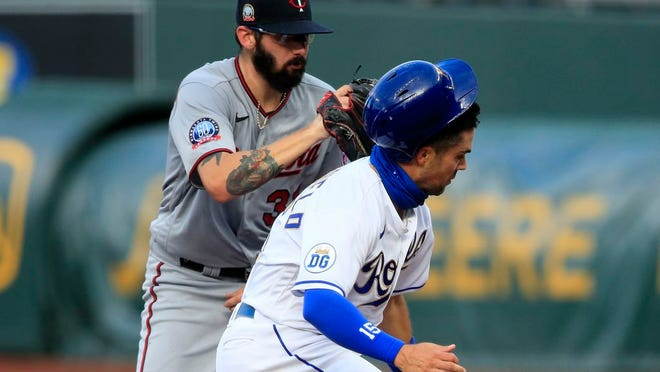 Kansas City Royals' Whit Merrifield, right, is tagged out by Minnesota Twins starting pitcher Devin Smeltzer, left, during a rundown in the first inning of a baseball game at Kauffman Stadium in Kansas City, Mo., Friday, Aug. 7, 2020.