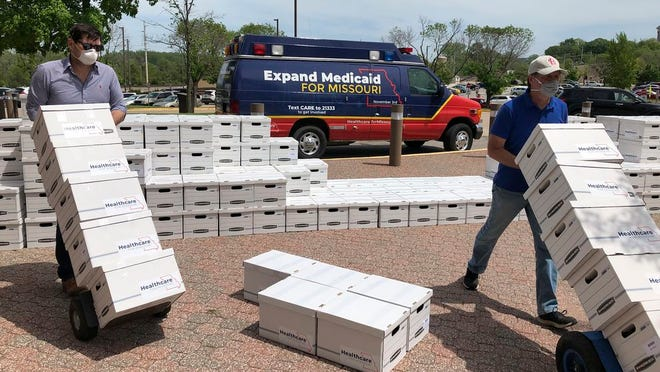 """FILE - In this May 1, 2020, file photo, campaign workers David Woodruff, left, and Jason White, right, deliver boxes of initiative petitions signatures to the Missouri secretary of state's office in Jefferson City, Mo. President Donald Trump is still trying to overturn """"Obamacare,"""" but his predecessor's health care law keeps gaining ground in places where it was once unwelcome. Missouri voters this week approved Medicaid expansion by a 53% to 47% margin, making the conservative state the seventh to do so under Trump."""