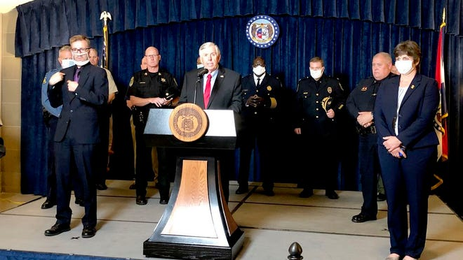 File - Missouri Gov. Mike Parson, center, is joined by state and local law enforcement officials Wednesday, July 15, 2020, where he announced that he is calling a special legislative session to begin July 27 to consider proposals intended to fight a rise in violent crime, during a news conference in the Missouri Capitol in Jefferson City.