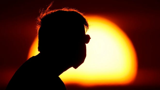 File - A man wearing a face mask to help prevent the spread of the coronavirus watches the sunset from a park in Kansas City, Mo., Friday, June 26, 2020.