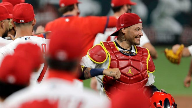 FILE - In this Friday, July 24, 2020, file photo, St. Louis Cardinals catcher Yadier Molina, right, celebrates a 5-4 win over the Pittsburgh Pirates in a baseball game in St. Louis. Molina says he's one of the players on his team who has tested positive for the coronavirus. The nine-time All-Star revealed his diagnosis Tuesday, Aug. 4, 2020, in a Spanish-language Instagram post.