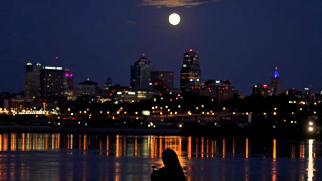 A woman watches as the full moon rises beyond downtown buildings Sunday, Aug. 2, 2020, in Kansas City, Mo.
