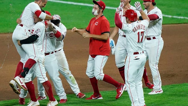 Cincinnati Reds teammates celebrate after defeating the Kansas City Royals in a baseball game at Great American Ballpark in Cincinnati, Tuesday, Aug. 11, 2020.